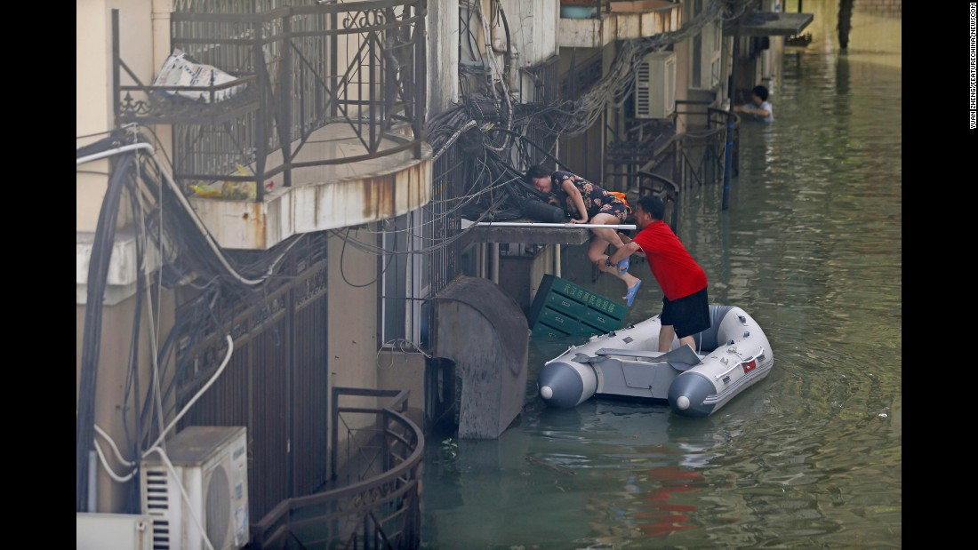 A man helps a women climb onto a building after flooding in China's Hubei province on Friday, July 8.