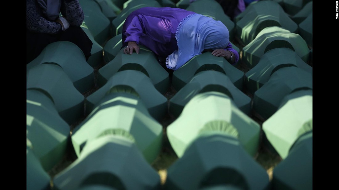 "A Bosnian woman prays next to a coffin containing the remains of a relative who perished in the <a href=""http://www.cnn.com/2015/07/11/europe/srebrenica-massacre-bosnians/"" target=""_blank"">Srebrenica massacre</a> -- the genocidal killing of more than 8,000 Bosniaks during the Bosnian War in July 1995 -- during a funeral near Srebrenica on Monday, July 11."