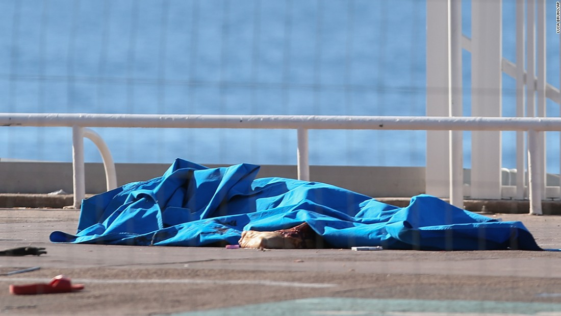 Bodies of victims covered by sheets remained at the scene of the attack early Friday.