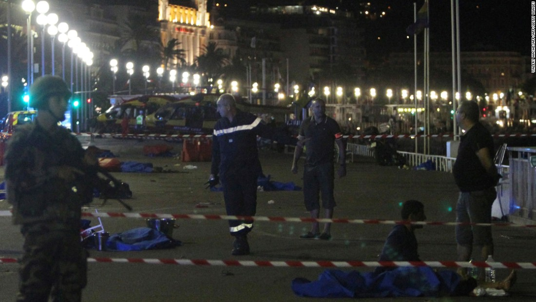 Soldiers, police officers and firefighters walk among bodies covered with blue sheets on the seafront Promenade des Anglais.