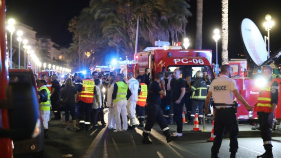 "Police officers, firefighters and rescue workers are seen at the site of an attack on July 15, 2016, after a truck drove into a crowd watching a fireworks display in the French Riviera town of Nice. A truck ploughed into a crowd in the French resort of Nice on July 14, leaving at least 60 dead and scores injured in an ""attack"" after a Bastille Day fireworks display, prosecutors said on July 15.  / AFP / Valery HACHE        (Photo credit should read VALERY HACHE/AFP/Getty Images)"