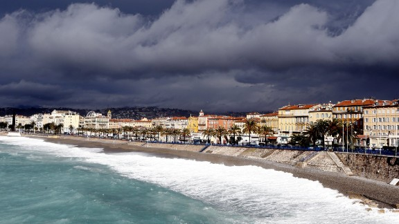 Waves break on the beach below the Promenade des Anglais as clouds gather above the French Riviera city of Nice.