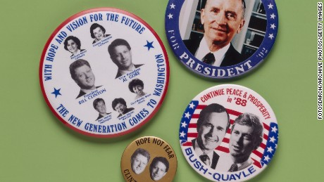 Badges for the 1988 election are pictured. The badges feature candidates Bill Clinton and Al Gore  (Democrats), George Bush and Dan Quayle (Republicans), and Ross Perot.