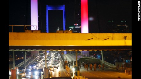 "Turkish soldiers block Istanbul's iconic Bosporus Bridge on Friday, July 15, 2016, lit in the colours of the French flag in solidarity with the victims of Thursday's attack in Nice, France. A group within Turkey's military has engaged in what appeared to be an attempted coup, the prime minister said, with military jets flying over the capital and reports of vehicles blocking two major bridges in Istanbul. Prime Minister Binali Yildirim told NTV television: ""it is correct that there was an attempt,"" when asked if there was a coup."