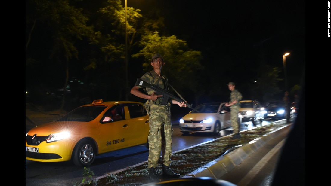 A Turkish security officer stands guard on the side of the road.
