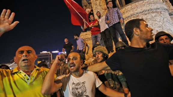 Supporters of President Recep Tayyip Erdogan protest in front of soldiers in Istanbul's Taksim Square.