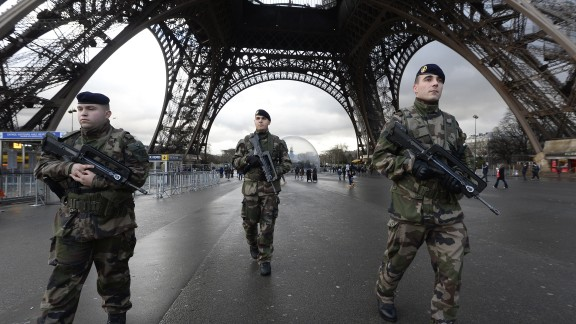French soldiers patrol in front of the Eiffel Tower on January 8, 2015 in Paris as the capital was placed under the highest alert status a day after heavily armed gunmen shouting Islamist slogans stormed French satirical newspaper Charlie Hebdo and shot dead at least 12 people in the deadliest attack in France in four decades. A  huge manhunt for two brothers suspected of massacring 12 people in an Islamist attack at a satirical French weekly zeroed in on a northern town Thursday after the discovery of one of the getaway cars. As thousands of police tightened their net, the country marked a rare national day of mourning for Wednesday