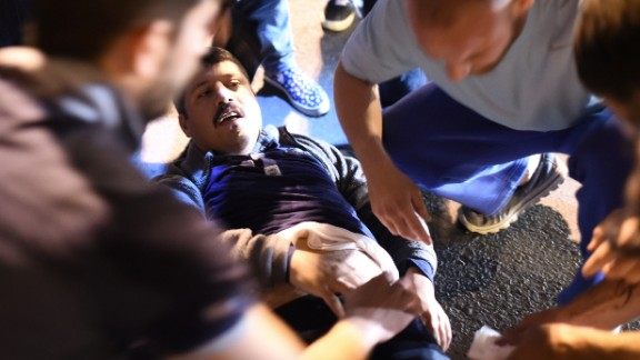 A wounded man is given medical care at the entrance to the Bosphorus Bridge in Istanbul after clashes with Turkish military.
