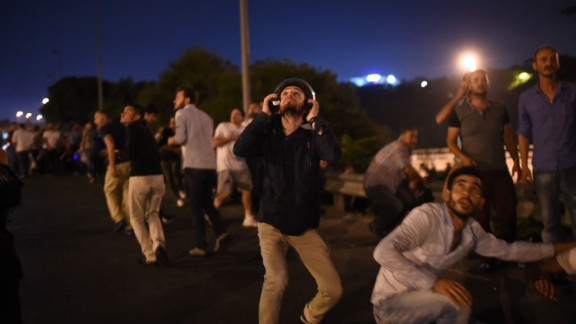People take cover near the Bosphorus Bridge as military airplanes fly overhead.