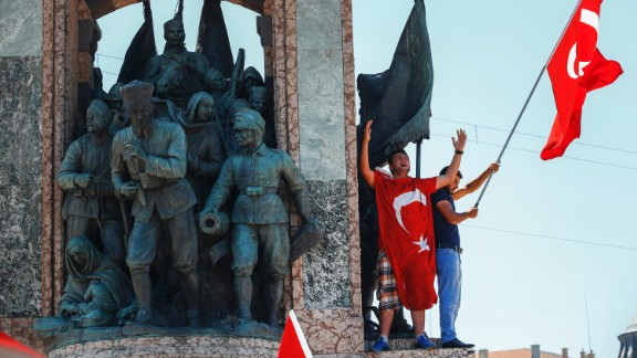 People protesting against the coup wave a Turkish flag on top of a monument in Istanbul