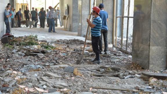 Workers clean up debris at Turkish parliament in Ankara.