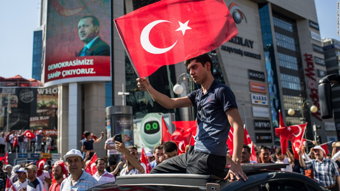 A man waves a Turkish flag from a car roof during a July 16 march around Kizilay Square in Ankara after the attempted military coup.