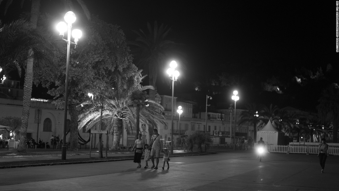 People hold hands as they walk on the Promenade des Anglais.