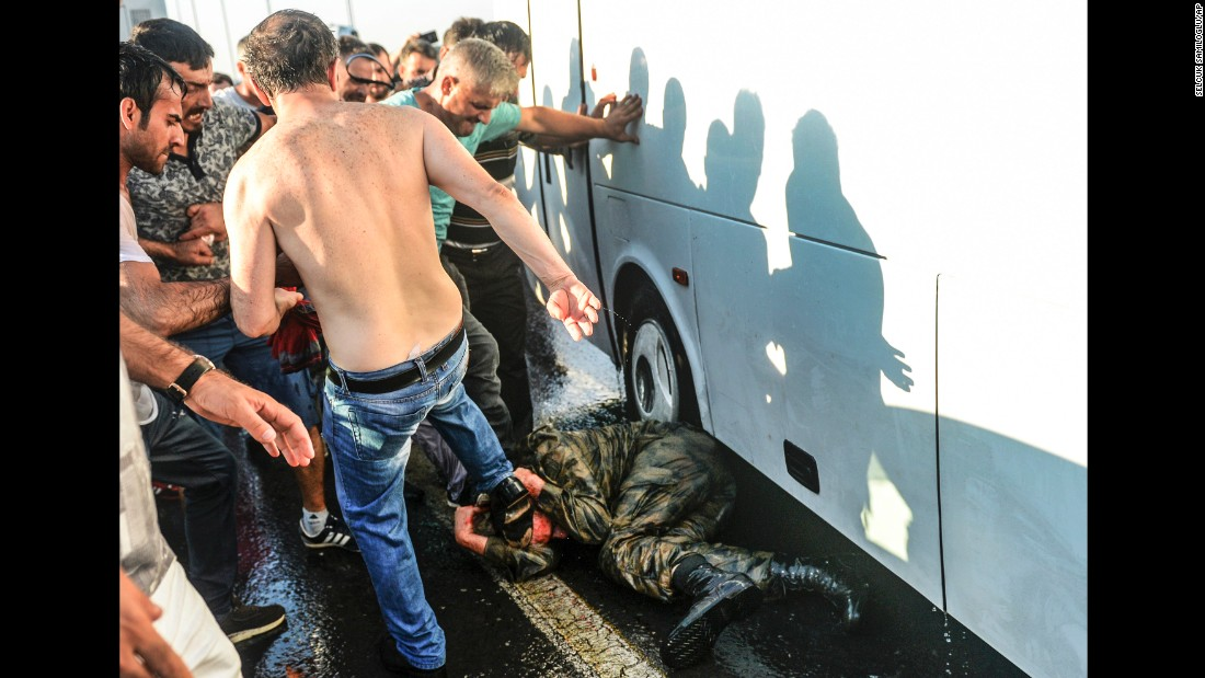 People kick and beat a Turkish soldier suspected in the attempted coup on Istanbul's Bosphorus Bridge on July 16.