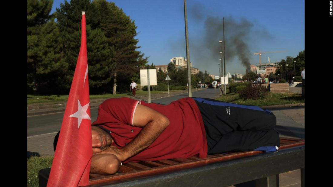 A protester rests on a bench as smoke billows from the Turkish military headquarters in Ankara.