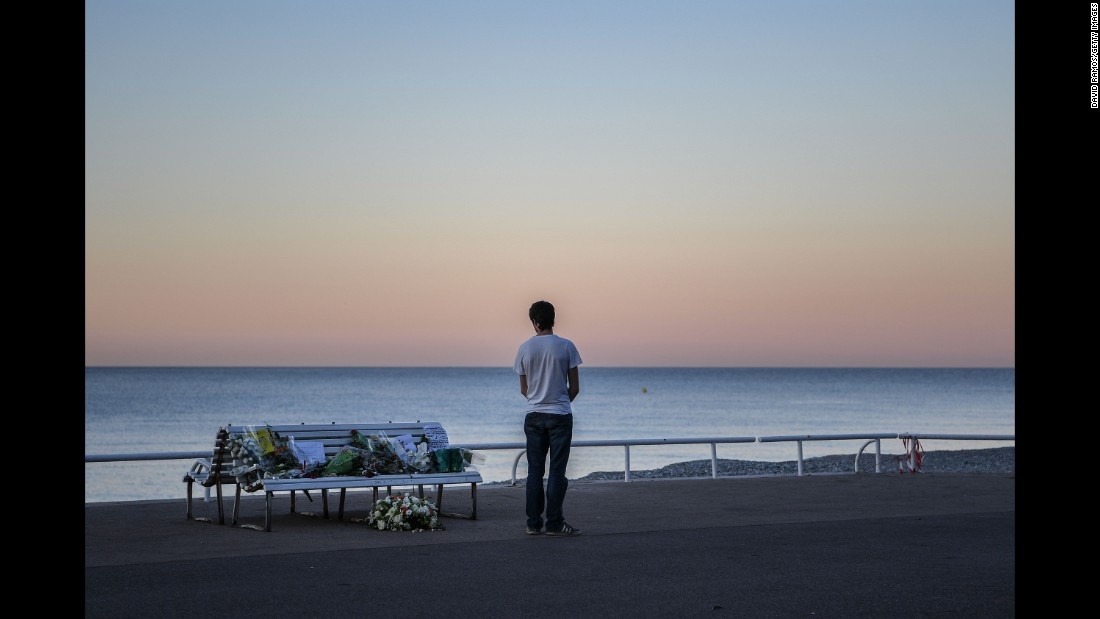 A man takes in a tribute to the Nice victims left on a bench near the site of the attack on the Promenade des Anglais on July 17.