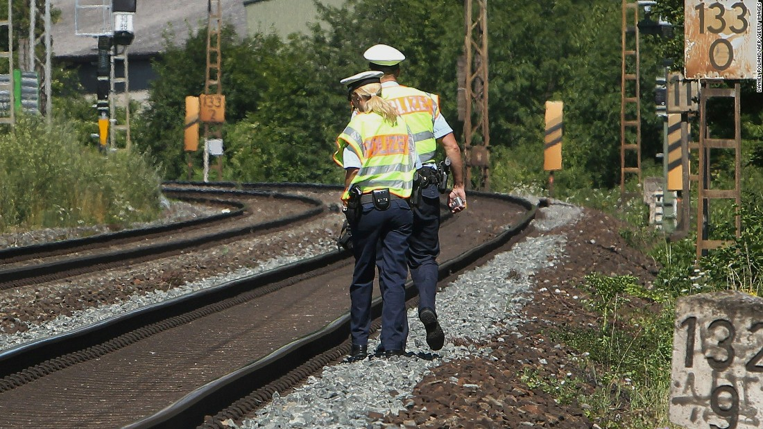 "Officers walk along train tracks in Wurzburg on July 19, a day after the attack. German authorities said they had found a hand-drawn flag resembling the one used by ISIS among the Afghan man's belongings. A pro-ISIS media group said the attacker was an ""ISIS fighter,"" but authorities cast doubt on that claim."