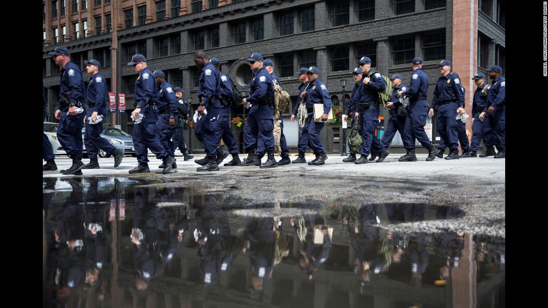 Police officers walk to designated protest areas on Monday.