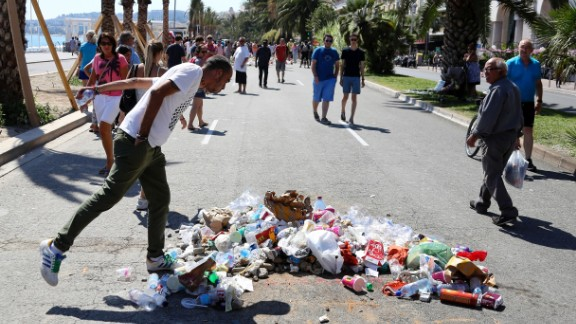 """A man spits on July 18, 2016 on the Promenade des Anglais seafront in Nice, at the site where Mohamed Lahouaiej-Bouhlel, a 31-year-old Tunisian who drove a truck into a crowd watching a fireworks display on Bastille Day, was killed by the police. The message reads """"coward"""". France was set to hold a minute's silence on July 18, 2016 to honour the 84 victims of the Nice truck attack, but a period of national mourning was overshadowed by bickering politicians. Church bells will toll across the country, and the country will fall silent at midday, a now grimly familiar ritual after the third major terror attack in 18 months on French soil. / AFP / Valery HACHE        (Photo credit should read VALERY HACHE/AFP/Getty Images)"""