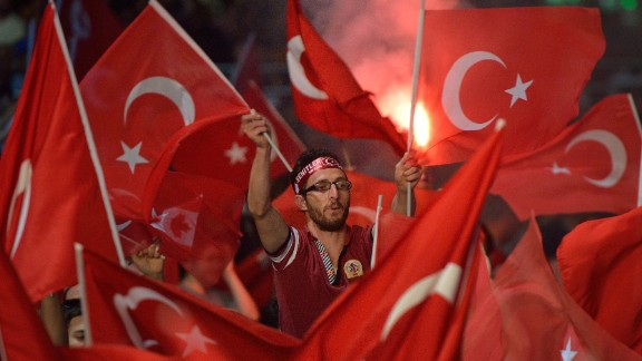 TOPSHOT - A man waves a Turkish flags during a meeting in support of the Turkish president on Taksim Square in Istanbul on July 19, 2016. Turkey widened its massive post-coup purge to schools and the media on July 19, vowing to root out supporters of an exiled Islamic cleric it accuses of orchestrating the attempted power grab. / AFP PHOTO / DANIEL MIHAILESCUDANIEL MIHAILESCU/AFP/Getty Images