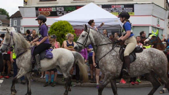 Horses convene up a side road and give the human racers a head start to avoid a Pamplona-style pell-mell at the starting line.