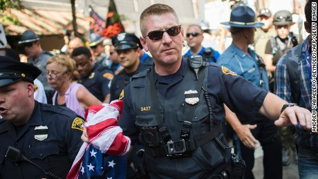 A policeman carrying a US national flag pushes people back as an activist  is arrested  during a protest outside the Republican National Convention in Cleveland, Ohio on July 20, 2016.
