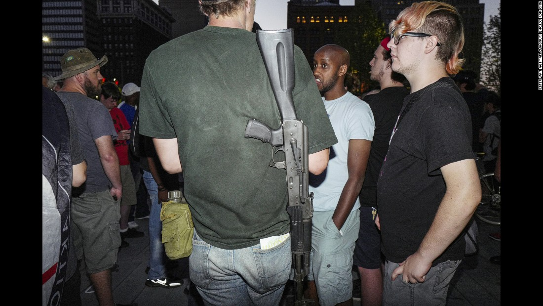 A calm conversation takes place in Public Square with a man wearing a gun.