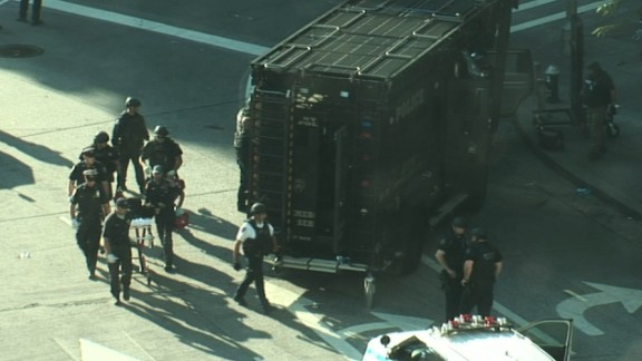 New York police on Thursday wheel away a man suspected of tossing a device into a marked police van.