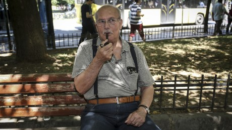 Ali, a teacher, smokes his pipe as he poses for a photo, in Istanbul.