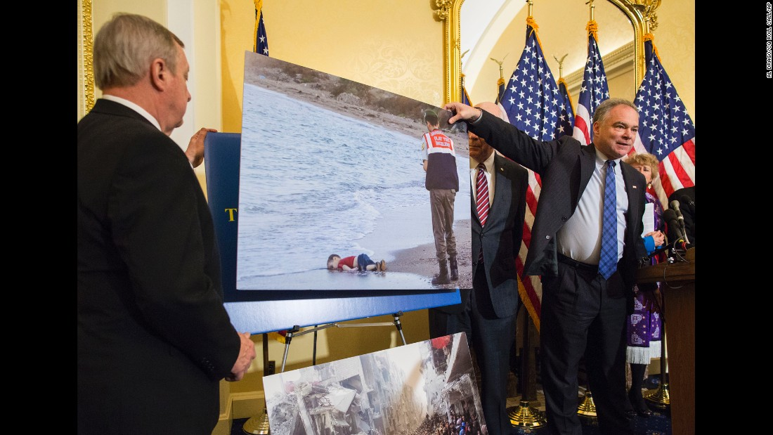Kaine shows the photo of a 3-year-old drowned Syrian boy during a Capitol Hill news conference in 2015. Politicians and religious leaders had come together to discuss the Syrian refugee crisis.