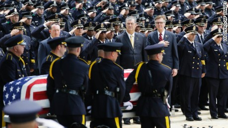Members of an honor guard carry the flag draped casket holding slain Dallas Police officer Michael Krol as Dallas Police Chief David Brown, center, looks on with Dallas Mayor Mike Rawlings, center right, and Texas Lt. Gov. Dan Patrick after a funeral service at Prestonwood Baptist Church in Plano, Texas, Friday, July 15, 2016. Krol was one of five police officers killed by a lone gunman during a protest in Dallas last week. (AP Photo/LM Otero)