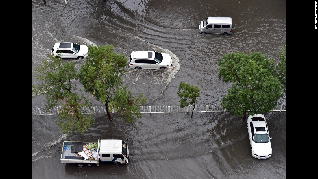 Vehicles drive on a flooded road in Tianjin, China, on Wednesday, July 20.