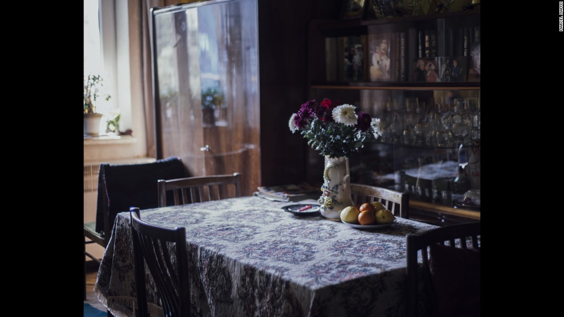 Inside Sauri's living room, where he and his wife have books, dishes and family pictures in a showcase beside the table.