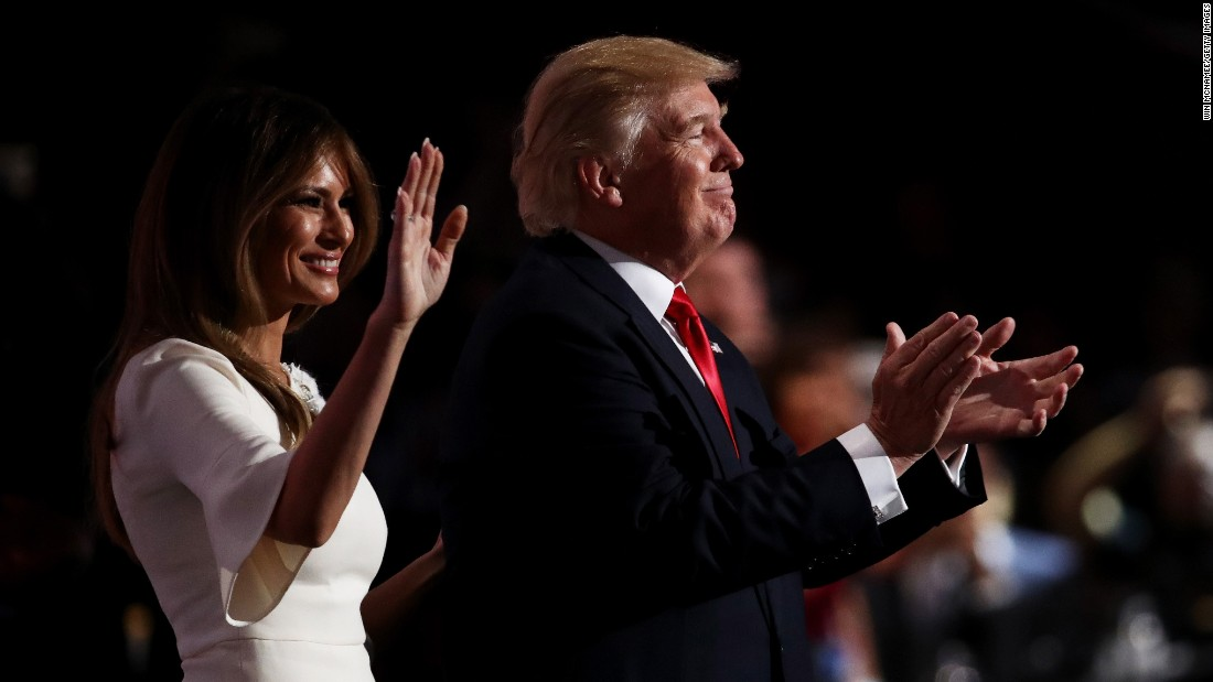 Trump claps on stage with his wife, Melania.