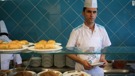 Ridvan, who works as a cook, helps a customer, in Istanbul.