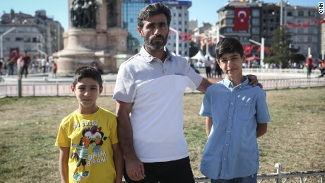 Taner, a construction worker, poses for a photo with his sons in Taksim Square, in Istanbul.