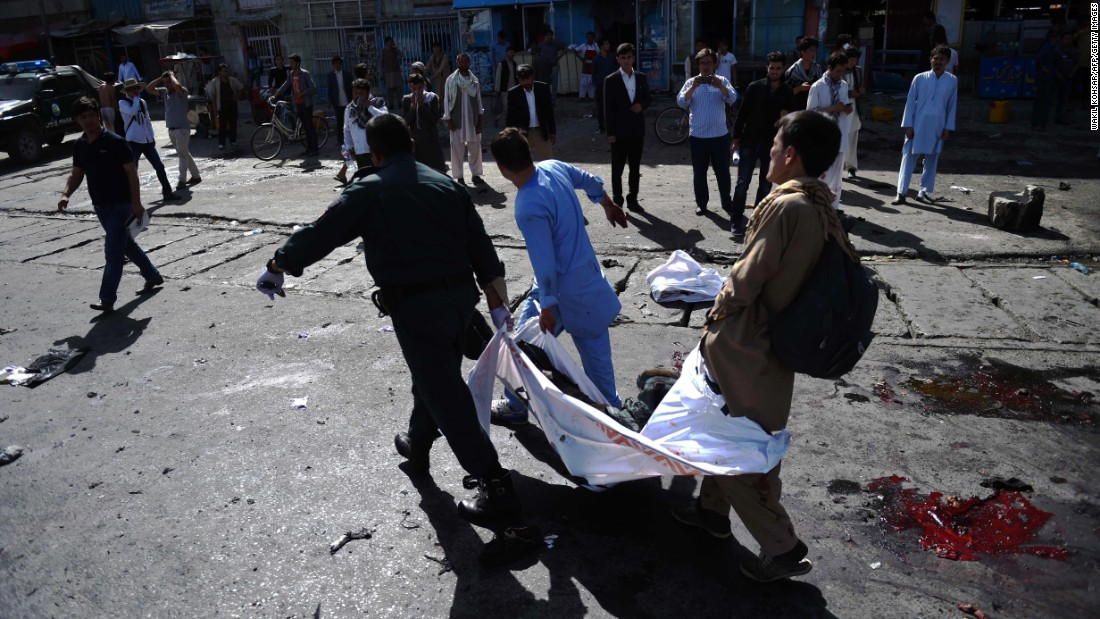 Afghan volunteers carry the bodies of victims.