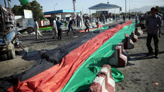 A banner in the colors of the Afghan flag is used to cover victim