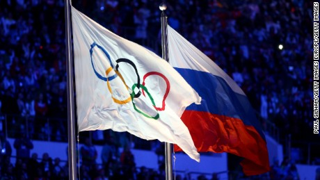The Olympic flag and Russian flag are raised as the Russian National Anthem is sung during the 2014 Sochi Winter Olympics Closing Ceremony.