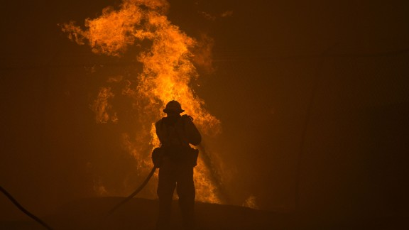 A firefighter hoses down burning pipes near a water tank.