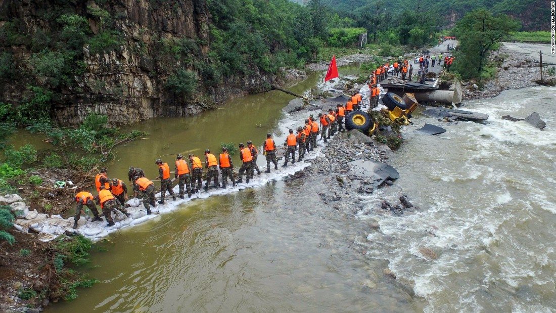 This photo taken on July 21 shows Chinese soldiers carrying sandbags to reinforce a damaged road hit by heavy rainstorms in Fangshan District in Beijing.
