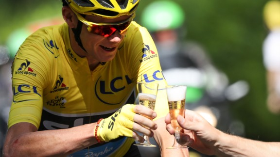 Froome drinks a glass of champagne as he rides at the start of the 113 km 21st and last stage of the 2016 Tour.