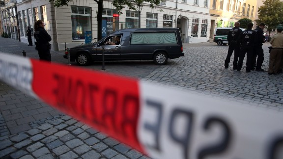 Police watch a hearse leave the scene of a suicide attack in the southern German city of Ansbach on 25 June, 2016  A Syrian migrant set off an explosion at a bar in southern Germany that killed himself and wounded a dozen others late Sunday, authorities said, the third attack to hit Bavaria in a week. The 27-year-old, who had spent a stint in a psychiatric facility, had intended to target a music festival in the city of Ansbach but was turned away because he did not have a ticket.  / AFP / dpa AND DPA / Daniel Karmann / Germany OUT        (Photo credit should read DANIEL KARMANN/AFP/Getty Images)