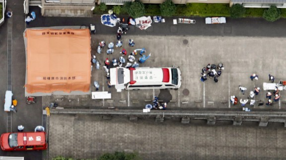 Ambulance crews are seen working outside the facility, now the site of one of Japan