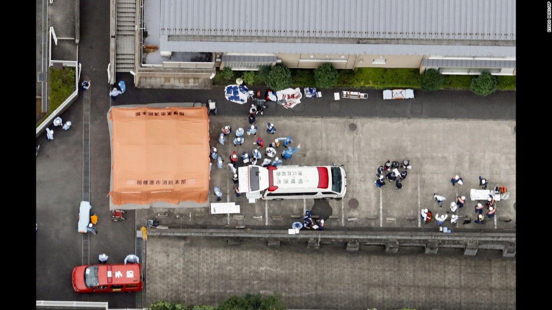 Ambulance crews are seen working outside the facility, now the site of one of Japan's deadliest mass killings since World War II.