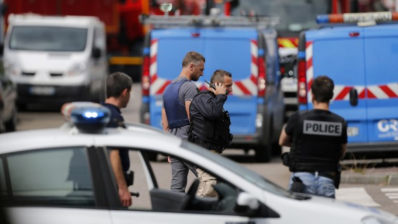 French police officers and firemen arrive at the scene of a hostage-taking at a church in Saint-Etienne-du-Rouvray, northern France, on July 26, 2016 that left the priest dead. A police source meanwhile confirmed that police killed two hostage-takers.