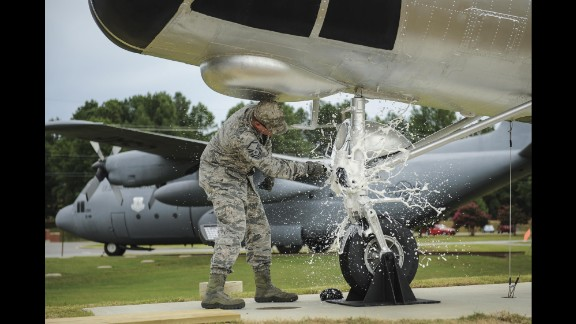 """Air Force Master Sgt. Matthew Tabor breaks a bottle to christen an H-21B helicopter while wearing the """"tiger-stripe"""" Airman Battle Uniform in July."""