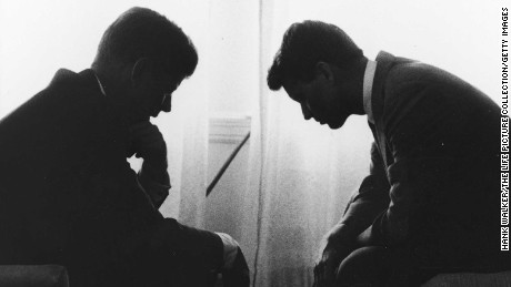 Presidential candidate John F. Kennedy conferring w. his brother & campaign organizer Bobby Kennedy in hotel suite as they are silhouetted by the sunlight coming through the drawn window drapes .
