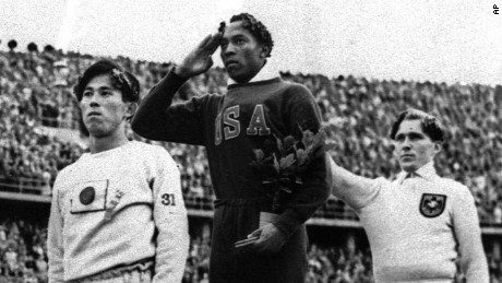 Olympic broad jump medalists salute during the medals ceremony Aug. 11, 1936 at the Summer Olympics in Berlin.  From left on podium are: bronze medalist Jajima of Japan, gold medalist Jesse Owens of the United States and silver medalist Lutz Long of Germany.  Long and German Olympic officials give the Nazi salute, while Owens gives a traditional salute.