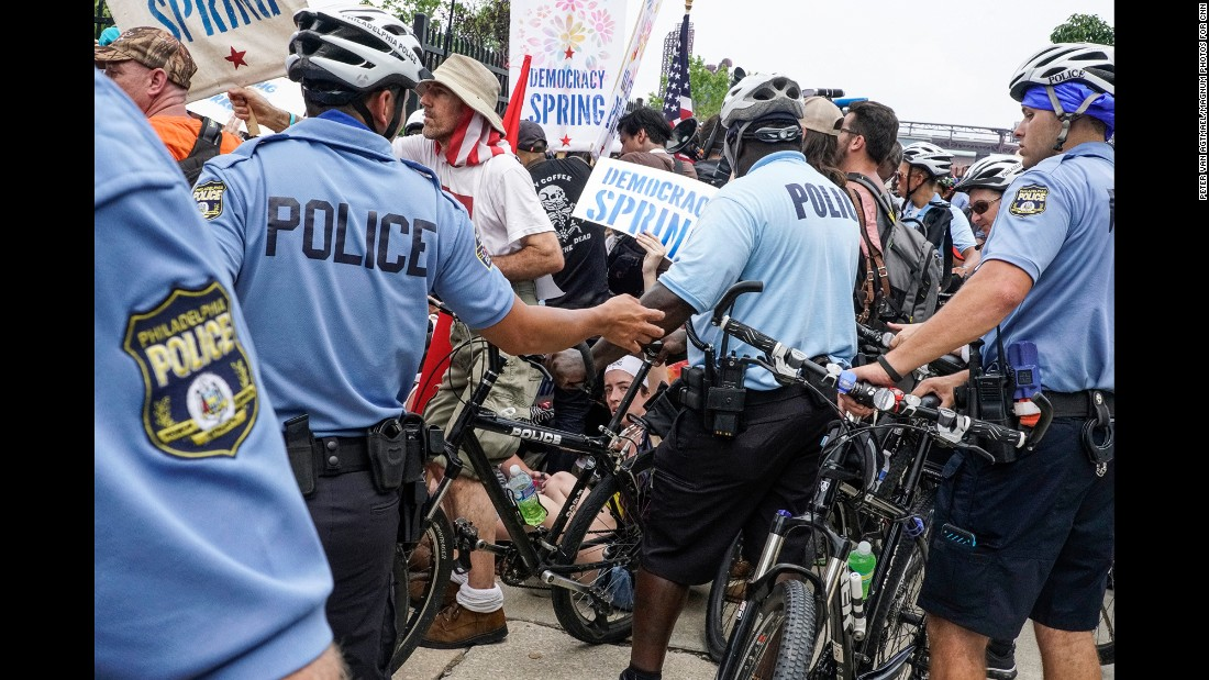 Police surround demonstrators during a sit-in outside a delegate entry point.